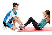 image of helping others  - Teenagers boy and girl helping each other working out abs crunches on a mat - JPG