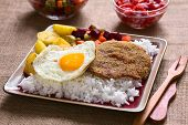 picture of flat-bread  - Traditional Bolivian dish called Silpancho which is the name of the breaded flat round piece of beef meat served with fried egg rice fried potatoes and vegetables  - JPG