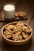 stock photo of cookie  - Chocolate chip cookies in wooden bowl with a glass of cold milk in the back photographed on wood with natural light  - JPG