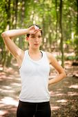 image of forehead  - Young woman tired after jogging in forest wipes her forehead - JPG