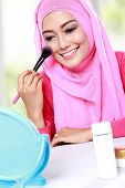 image of muslimah  - portrait of cheerful young woman looking at the mirror while applying blush on - JPG