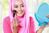 picture of muslimah  - portrait of cheerful young woman looking at the mirror while applying blush on - JPG