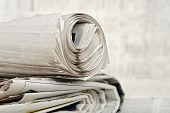 picture of newspaper  - rolled newspaper on stack of newspapers against blurry background - JPG