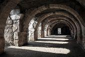 stock photo of empty tomb  - Interior of empty dark corridor with arcs - JPG