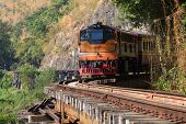foto of train track  - trains running on death railways track crossing kwai river in kanchanaburi thailand this railways important destination of world war II history builted by soldier prisoners - JPG