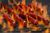 image of flame-grilled  - Hotdogs cooking on a barbecue grill with hot flame - JPG