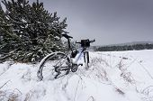 picture of dirt-bike  - bike off the trail buried in snow in winter scenery - JPG