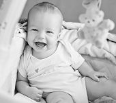 picture of bassinet  - happy baby sitting in bed looking at the camera  - JPG
