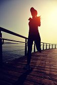 Постер, плакат: healthy lifestyle sports woman running on wooden boardwalk sunrise seaside
