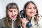stock photo of 7-year-old  - Seven year old girl talking on the old vintage phone and her sister eavesdropping her conversation - JPG