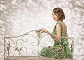 picture of sitting a bench  - Retro Woman Portrait Beautiful Lady with Wave Hairstyle Sitting in Elegant Dress Fashion Model Beauty Make Up with Curly Hair Style - JPG
