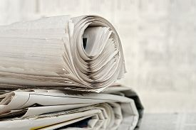 stock photo of brainwashing  - rolled newspaper on stack of newspapers against blurry background - JPG