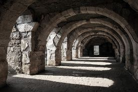 stock photo of empty tomb  - Interior of empty dark corridor with arcs - JPG