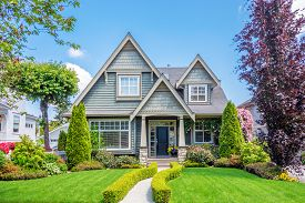 stock photo of in front  - Cozy house with beautiful landscaping on a sunny day - JPG