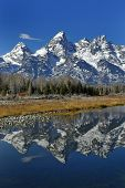pic of mountain-range  - teton mountain range reflecting in river water with surrounding plants and trees - JPG
