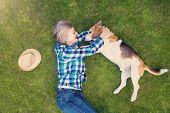 stock photo of beautiful senior woman  - Beautiful senior woman with a dog lying on a grass - JPG