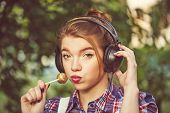pic of lollipop  - Portrait of a young attractive hipster girl headphones and a lollipop - JPG