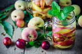 stock photo of infusion  - Jar delicious refreshing drink of peach fruits and plum with mint on wooden infused water - JPG