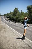 pic of short legs  - Young beautiful woman in short shorts hitchhiking along a road - JPG