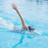 image of crawling  - Young girl in goggles and cap swimming front crawl stroke style in the blue water pool - JPG