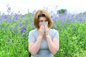 stock photo of rhinitis  - An adult woman with allergies on the Meadow - JPG