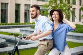 pic of opposites  - Young couple sitting on a bicycle opposite the green city park - JPG