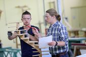 foto of carpentry  - Apprentice with adult in carpentry school working on wood - JPG