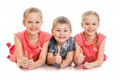 picture of little sister  - Two sisters and little brother lying on the floor  - JPG