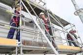 stock photo of scaffold  - Construction workers installing scaffolding on site - JPG