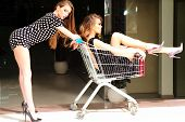 image of trolley  - Two sexual fashionable women in dresses with shopping trolley indoor on shop background horizontal picture - JPG