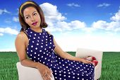 picture of surrealism  - black female in a vintage polka dot dress in a surreal outdoors setting - JPG