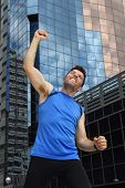 picture of victory  - young attractive sport man doing victory and winner sign with his arms after running training in urban business district area in fitness body care and healthy lifestyle concept - JPG