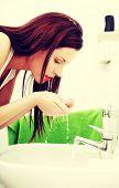 image of bathroom sink  - Woman splashing face with water above bathroom sink - JPG
