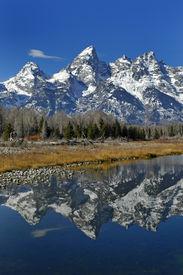stock photo of mountain-range  - teton mountain range reflecting in river water with surrounding plants and trees - JPG