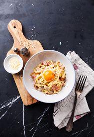 image of carbonara  - Pasta Carbonara with parmesan and yolk on dark marble background - JPG