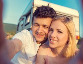 pic of camper  - Beautiful young couple in front of a camper van on a summer day - JPG
