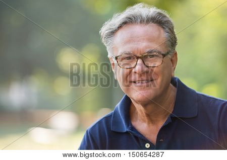 poster of Portrait of senior man smiling and loooking at camera. Face of a happy old man wearing eyeglasses ou