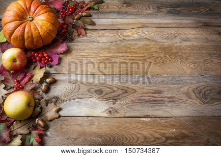 poster of Thanksgiving or fall greeting with pumpkins and fall leaves on blue background. Fall background. Thanksgiving background with seasonal vegetables and fruits. Copy space