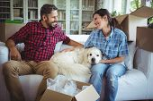 Couple sitting on sofa with their pet dog in their new house poster