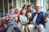 Happy family watching television in living room at home poster