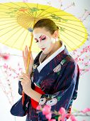 Artistic Portrait Of Japan Geisha Woman With Creative Make-up Near Sakura Tree In Kimono With Umbrel