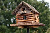 Handcrafted log cabin birdhouse.  Close-up with shallow dof.
