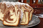 Freshly baked cinnamon swirl coffee cake with cherry topping and tableware in background.  Closeup w