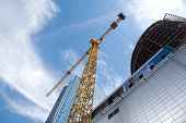 stock photo of erection  - Modern building under construction against blue sky - JPG