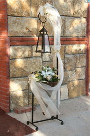 image of ecclesiastical clothing  - beautiful church candle with bows and flowers for wedding near the wall - JPG