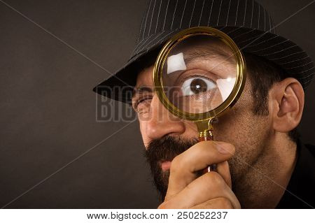 poster of The Curious Detective Is Looking With Magnifier Or Magnifying Glass Or Loupe On Dark Gray Background