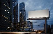 Blank Billboard At Night Time In The City Next To Skyscrapers And Road With Lights On The Frame. 3d  poster