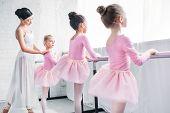 Cute Little Kids In Tutu Skirts Exercising With Teacher In Ballet School poster