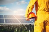 Clean Energy Concept.electrical Worker Or Engineer Holding Safety Hat Stand At Solar Panel Backgroun poster