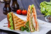 Club Sandwich With Cheese, Cucumber, Tomato, Chicken Meat And Lettuce On Dark Wooden Table. Deliciou poster